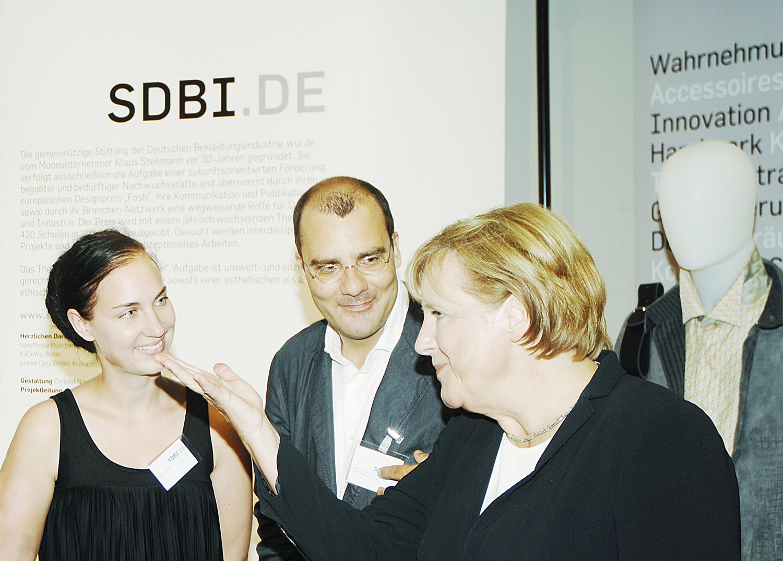 """Bianca Koczan (1. Preis FASH 2006) und SDBI-Projektleiter Joachim Schirrmacher stellen Bundeskanzlerin Angela Merkel die Nachwuchsarbeit der Stiftung der Deutschen Bekleidungsindustrie vor. Die SDBI war eingeladen zur Ausstellung """"Innovation in Deutschland"""" zum Tag der offenen Tür im Bundeskanzleramt."""