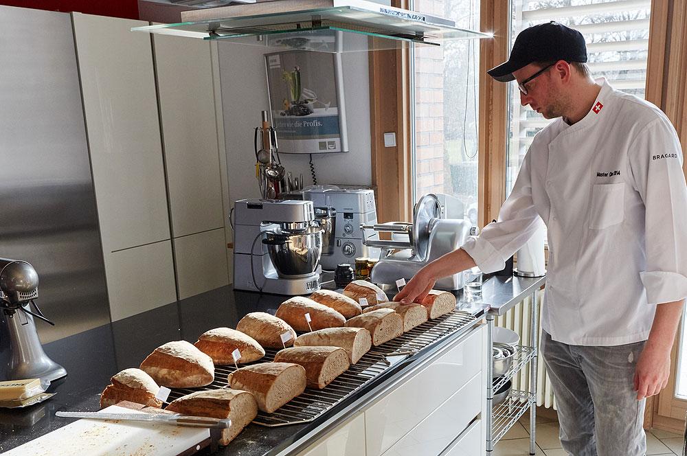Florian Schwitzke, Koch der Schweizer Botschaft, der auch in einer Bäckerei gelernt hat beurteilt die Brote. Foto: © Bernhard Ludewig