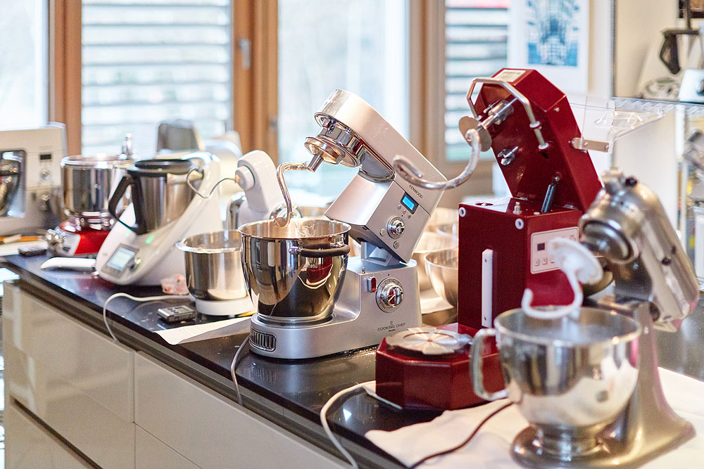Die Knetmaschinen vor dem Test. Von links: Ankarsrum, Thermomix, Bosch Mum, Kenwood Cooking Chef, Häussler, Kitchenaid. Foto: © Bernhard Ludewig